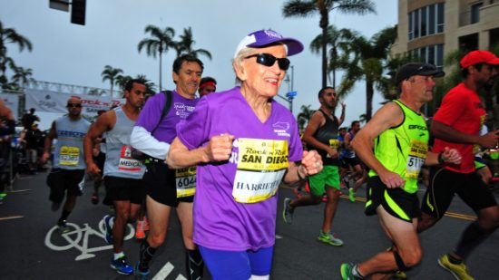 In this photo provided by Competitor Group, Harriette Thompson starts the Suja Rock 'n' Roll Marathon in San Diego on Sunday, May 31, 2015. Thompson, of Charlotte, N.C., is a two-time cancer survivor who dealt with the loss of her husband and a staph infection in her legs while training for this year's race. If she completes the race she would become, at age 92 years and 65 days, the oldest woman to ever complete a marathon. Her son Brenny Thompson is behind her in the purple shirt. (Paul Nestor/Competitor Group via AP)