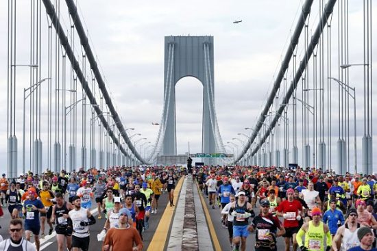 Police and U.S. Coast Guard helicopters fly overhead as runners cross the Verrazano-Narrows Bridge at the start of the New York City Marathon, Sunday, Nov. 3, 2013, in New York. (AP Photo/Jason DeCrow)