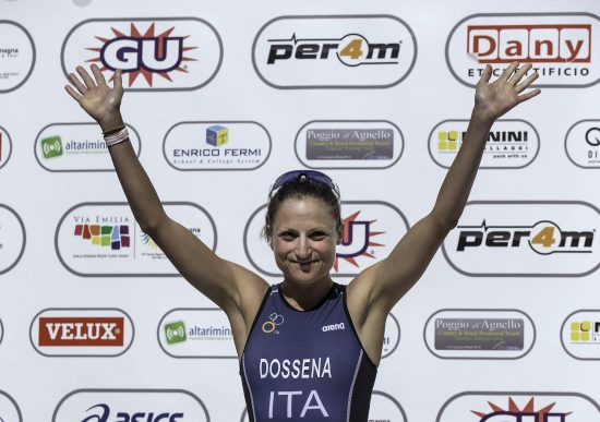 RIMINI, ITALY - MAY 24: Female athlete Sara Dossena from Italy, second placed, waves at the top three podium during the award ceremony after the 2015 ETU Challenge Rimini European Championship Half Distance on May 24, 2015 in Rimini, Italy. (Photo by Gonzalo Arroyo Moreno/Getty Images)