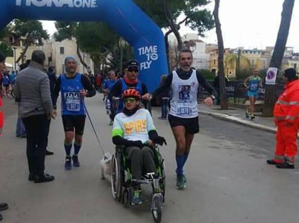 Squalificato runner perché spinge la carrozzina del figlio disabile insieme al cane!