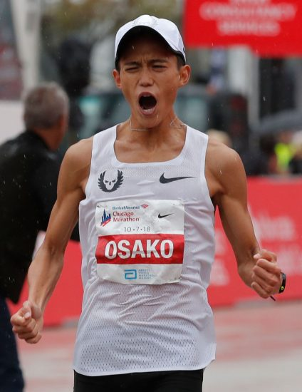 "CORRECTION - Suguru Osako of Japan reacts after finishing third in the Chicago Marathon in Chicago, on October 7, 2018. - British athletics star Mo Farah won the Chicago Marathon men's title on Sunday in an unofficial time of 2hr 5min 11sec, shattering a European record with a spectacular finishing surge. The world and Olympic 5,000 and 10,000-meter champion became the first British man to capture the event since Paul Evans in 1996.The 35-year-old Somalia-born Briton claimed the biggest victory since he turned his attention to the distance a year ago to defeat Ethiopia's Mosinet Geremew by 13 seconds with Japan's Suguru Osako third in 2:05:50. (Photo by JIM YOUNG / AFP) / ""The erroneous mention appearing in the metadata of this photo by JIM YOUNG has been modified in AFP systems in the following manner: [Suguru Osako of Japan] instead of [Suguru Osaka of Japan]. Please immediately remove the erroneous mention from all your online services and delete it from your servers. If you have been authorized by AFP to distribute it to third parties, please ensure that the same actions are carried out by them. Failure to promptly comply with these instructions will entail liability on your part for any continued or post notification usage. Therefore we thank you very much for all your attention and prompt action. We are sorry for the inconvenience this notification may cause and remain at your disposal for any further information you may require."""