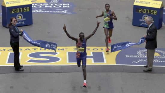 Lawrence Cherono, of Kenya, breaks the tape to win the 123rd Boston Marathon in front of Lelisa Desisa, of Ethiopia, right, on Monday, April 15, 2019, in Boston. (AP Photo/Charles Krupa)