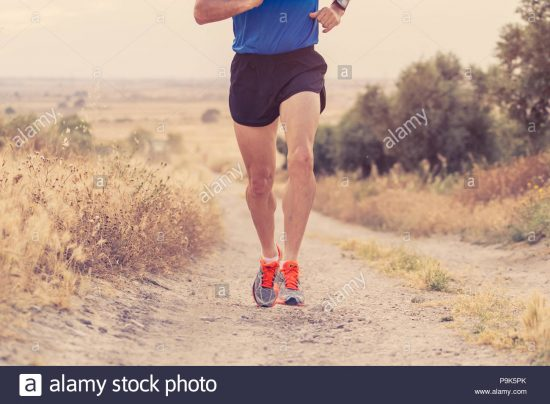 close-up-man-runner-legs-and-feet-of-extreme-cross-country-man-running-and-training-on-rural-track-jogging-at-sunset-with-harsh-sunlight-and-lens-flar-P9K5PK