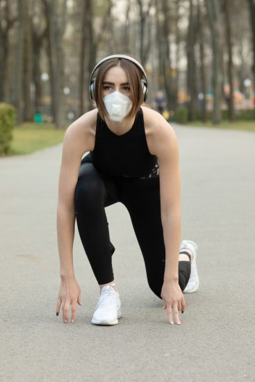 portrait-caucasian-sporty-woman-wearing-medical-protection-face-mask-while-running-park-corona-virus-covid-19-is-spreading-all-world_137441-817