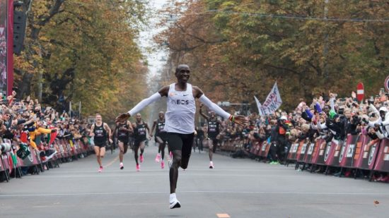 TOPSHOT - Kenya's Eliud Kipchoge (white jersey) celebrates as he crosses the finish line at the end of his attempt to bust the mythical two-hour barrier for the marathon on October 12 2019 in Vienna. - Kenya's Eliud Kipchoge on Saturday made history, busting the mythical two-hour barrier for the marathon on a specially prepared course in a huge Vienna park. With an unofficial time of 1hr 59min 40.2sec, the Olympic champion became the first ever to run a marathon in under two hours in the Prater park with the course readied to make it as even as possible. (Photo by ALEX HALADA / AFP) (Photo by ALEX HALADA/AFP via Getty Images)