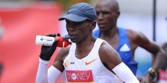 """Kenya's Eliud Kipchoge refuels during the elite men's race of the 2020 London Marathon in central London on October 4, 2020. - This year's London marathon, an elite-athlete only event, takes place in a """"secure biosphere"""" on a enclosed, looped course, in St James's Park, due to coronavirus restrictions. (Photo by Richard Heathcote / POOL / AFP) / """"Restricted to editorial use - sponsorship of content subject to LMEL agreement""""."""